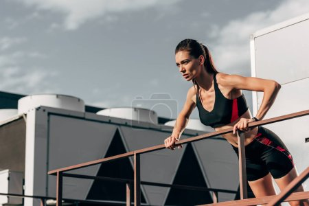 beautiful young sportswoman doing push up at railings on roof