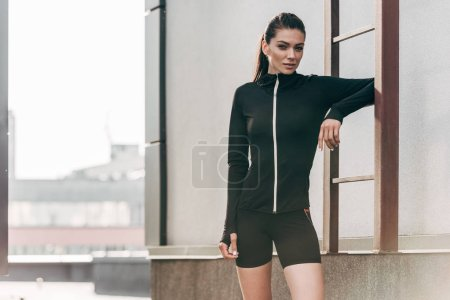 attractive sportswoman posing in thermal clothes near ladder on roof