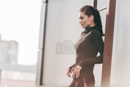 sportswoman posing in thermal clothes near ladder on roof