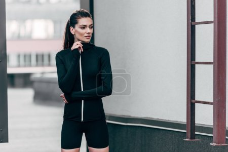 beautiful sportswoman posing in thermal clothes on roof