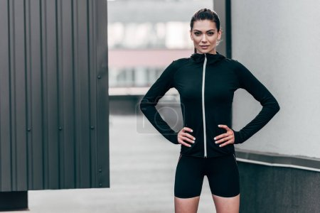 attractive sportswoman posing in thermal clothes on roof