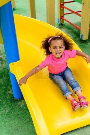 Photo pour Souriant frisé afro-américain petit enfant glissant vers le bas de colline à aire de jeux - image libre de droit
