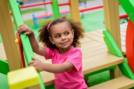 curly african american little child looking away playground