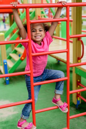 happy curly african american little child climbing on stairs at playground