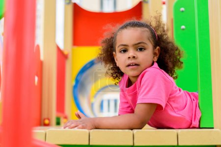 portrait of curly african american little child having fun at playground