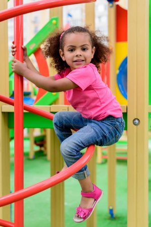 smiling curly african american little child having fun at playground