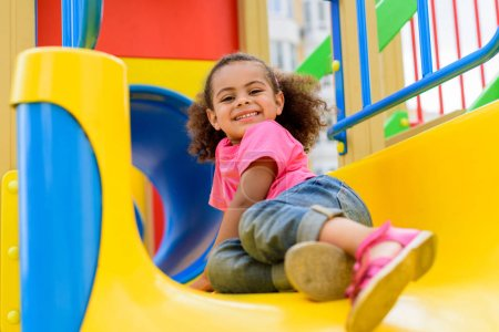 happy african american little kid sliding down from hill at playground