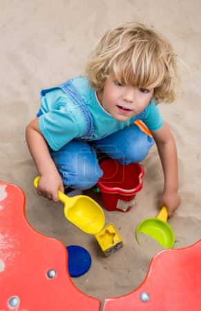 high angle view of little boy playing with plastic scoops, molds and bucket in sandbox at playgorund