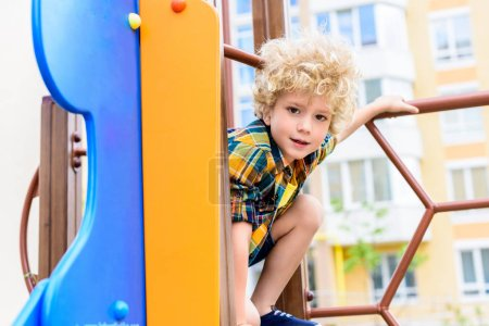 selective focus of adorable curly little boy having fun at playground