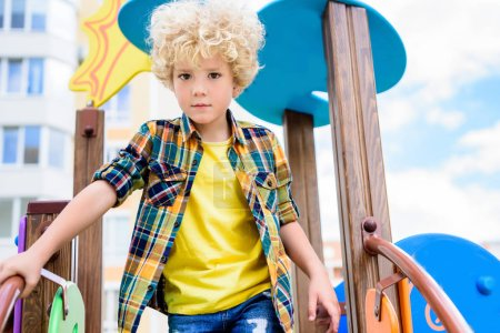 low angle view of adorable curly little boy having fun at playground