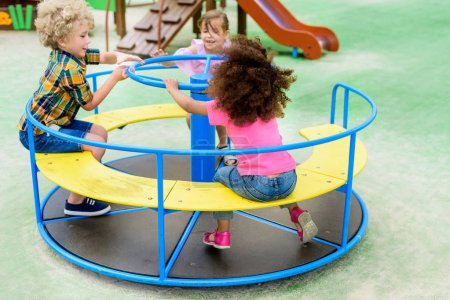 happy adorable little children riding on carousel at playground