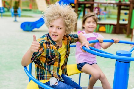 Photo for Adorable curly boy doing thumb up gesture while riding on carousel with little child at playground - Royalty Free Image