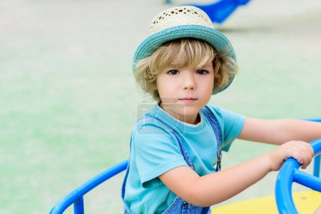 selective focus of adorable little boy in panama riding on carousel at playground