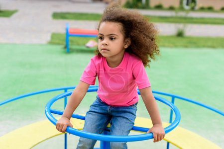 curly african american little child riding on carousel at playground