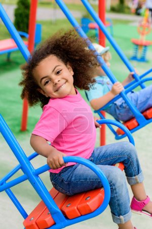 smiling curly african american little child riding on swing at playground