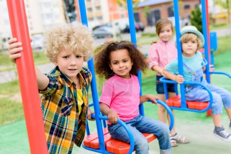 Photo for Multicultural group of little children riding on swings at playground - Royalty Free Image