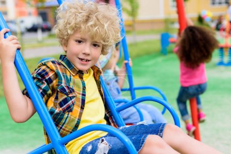 selective focus of happy curly little boy riding on swing at playground