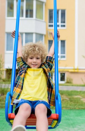 happy curly little boy riding on swing at playground