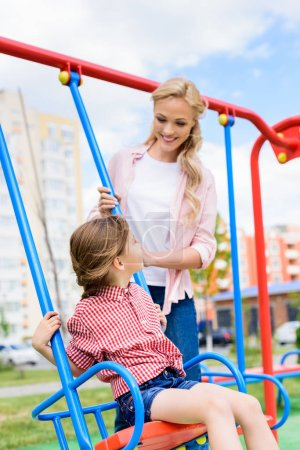 selective focus of smiling mother riding daughter on swing at playground