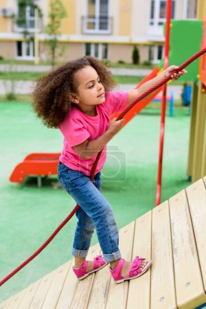 side view of curly african american little child climbing with rope at playground