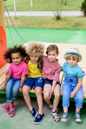high angle view of multiethnic group of adorable children embracing each other at playground