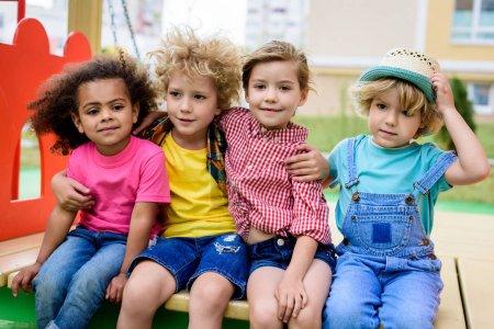 Foto de Adorable niño rizado abrazando a dos niños multiculturales mientras otro niño sentado junto a parque infantil - Imagen libre de derechos