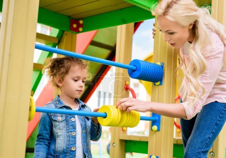 mother teaching to count little daughter on abacus at playground