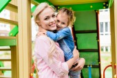 selective focus of happy mother holding adorable little daughter on hands at playground