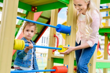 smiling mother teaching to count little daughter on abacus at playground