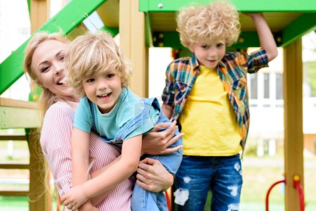 happy mother with two adorable playful little boys at playground
