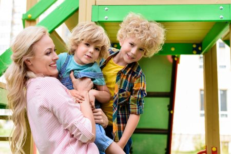 side view of smiling mother with two adorable little sons at playground
