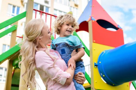 Photo for Low angle view of happy mother holding on hands smiling little son at playground - Royalty Free Image