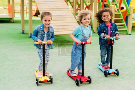 Photo for Three multicultural adorable little children riding on kick scooters at playground - Royalty Free Image