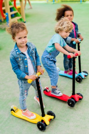 selective focus of multicultural adorable little children riding on kick scooters at playground
