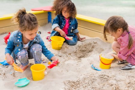 Photo for Three multiethnic little children playing with plastic scoops and buckets in sandbox at playground - Royalty Free Image