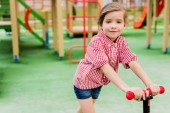 selective focus of little child riding on kick scooter at playground