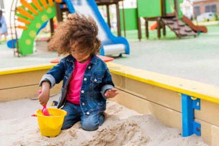 curly african american little child playing with plastic scoop and bucket in sandbox at playground