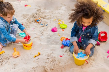 Photo for High angle view of two little multicultural children using plastic molds in sandbox at playground - Royalty Free Image