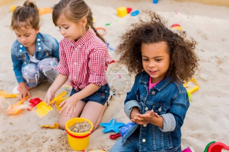 Photo for Selective focus of curly african american child playing wit friends in sandbox at playground - Royalty Free Image