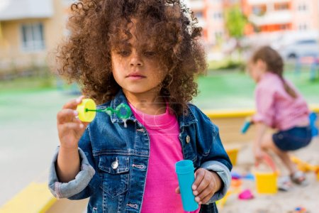 selective focus of curly african american little child playing with bubble blower