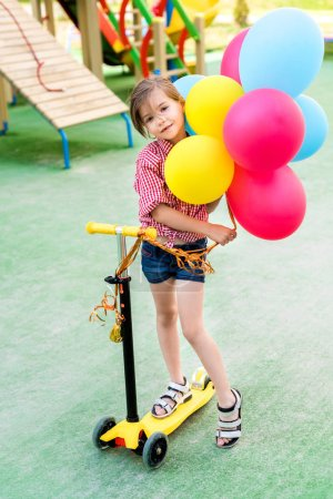 selective focus of little child riding on kick scooter with colorful balloons at playground