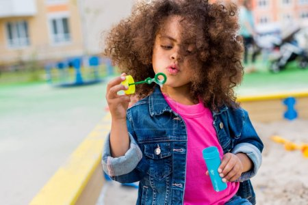 curly african american little child playing with bubble blower