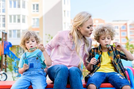 selective focus of mother sitting between two adorable little sons while they using bubble blowers on bench