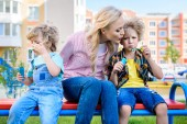 mother sitting between two adorable little sons while they using bubble blowers on bench