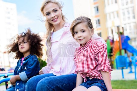 selective focus of smiling woman with daughter and her friend on bench