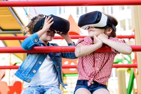 selective view of two little children using virtual reality headsets at playground