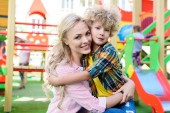 selective focus of happy mother embracing with adorable son at playground