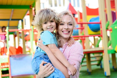 selective focus of happy mother holding adorable little son on hands at playground