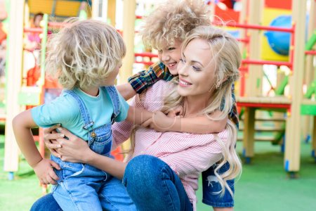 Photo for Happy mother embracing with two playful adorable sons at playground - Royalty Free Image