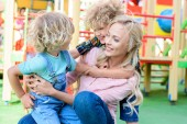happy mother embracing with two playful adorable sons at playground